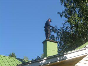 Nuohooja työssään katolla
